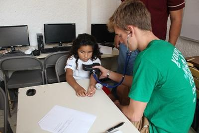 A young child gets a health check from a medical volunteer in Mexico