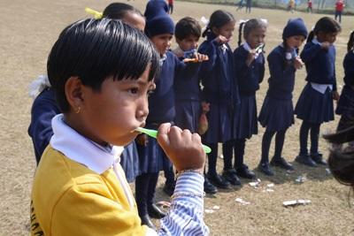 Volunteers teach Nepalese children how to care for their teeth at a medical outreach