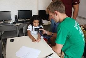 A Medicine volunteer measure a child's blood pressure during a healthcare outreach in Mexico.