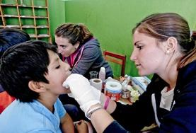 A Medicine intern examines a child during a medical outreach in Cusco, Peru.