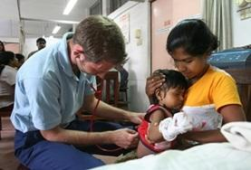 A Medicine volunteer performs a general check-up on a young child during a healthcare screening in Sri Lanka.