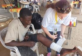 A Medicine volunteer assists with dressing a patient's wound durng her internship in Togo.