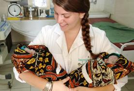 A Midwifery volunteer holds two newborn babies at her placement in the maternity department of a hospital in Tanzania.