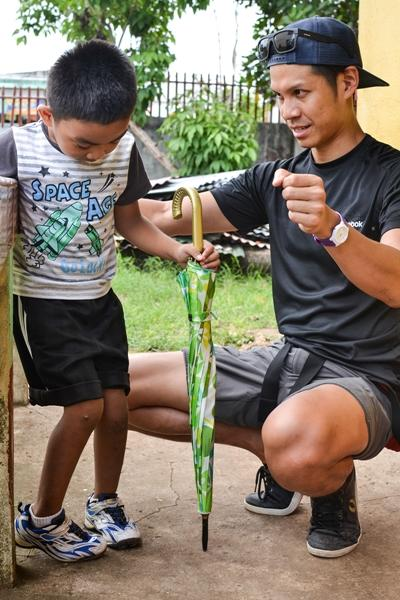 A volunteer administering physiotherapy to a young boy on a placement in the Philippines