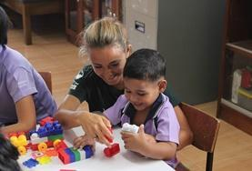 An Occupational Therapy volunteer works closely with a local child to improve his daily functioning during her Medical internship.