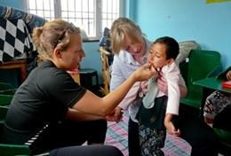 A volunteer doctor examines a patient on a placement in Nepal