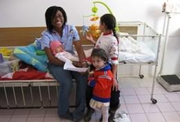 A volunteer Massage Therapist poses with children at a placement in Romania