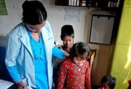 A Nursing volunteer stands with children at a placement in Nepal