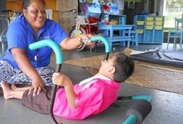 A professional Physiotherapist helps a disabled child through a specialised therapy exercise at her volunteer placement in Samoa.