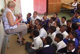 A professional Teacher works with a class of school students at her volunteer placement in South Africa.