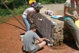 High School Special Building volunteers cover a brick wall with cement in a local community in Jamaica.