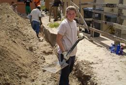 A High School Special volunteer holds a shovel at a Building placement in South Africa
