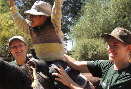 Equine Therapy High School Special volunteers assist a child riding a horse on a placement in Bolivia