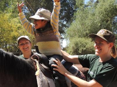 Two female volunteers help a child in Bolivia Equine therapy