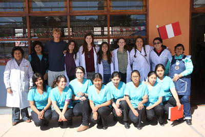 Short-term Special Medicine volunteers pose with teachers and nurses following a medical outreach at a primary school in Cusco