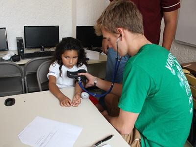 Volunteer inspecting a child in a medical outreach project in Mexico