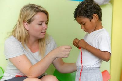 Local child gets help with an activity from a Projects Abroad Social Work intern in Ecuador