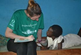 A Social Work intern works with a local child in Ghana under the guidance of a qualified mental health professional.