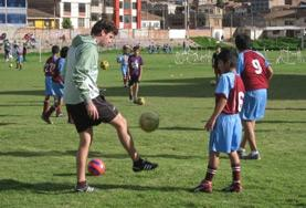 A volunteer plays soccer with local children