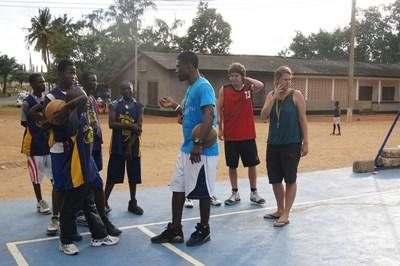 Basketball coaches and players talk on a court