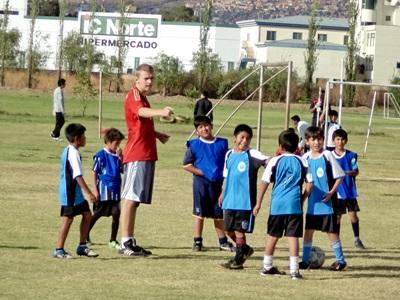 Young Bolivian children enjoy a soccer lesson with a Projects Abroad volunteer