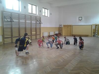 A volunteer helps children with a warm up in Romania