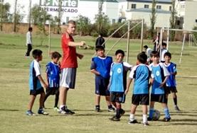 A Football volunteer coaches a local team of children in Bolivia, helping them work on their ball skills.