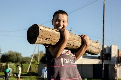 Young boy at the El Vagon sports school helps to carry logs to be used in building benches as part of a community day project in Cordoba, Argentina
