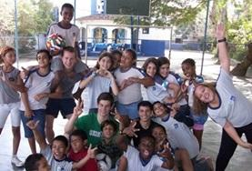 A local sports team poses together with the volunteer who has been coaching them at one of our Multi-sports placements.
