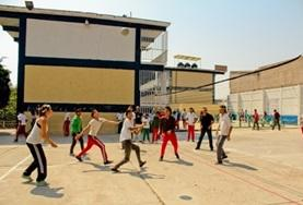 Volunteers and school children practise their volleyball skills during a sports practice.
