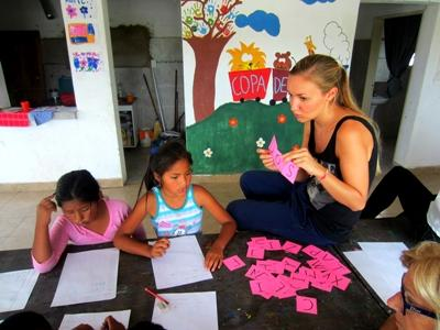A Projects Abroad volunteer helps two of her students at a school in Argentina, Latin America