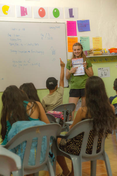 A volunteer at the teaching placement in San Cristobal helping a local child