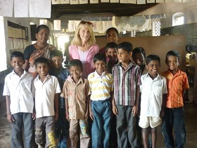 A volunteer poses with her class and colleagues at a school in India, Asia.