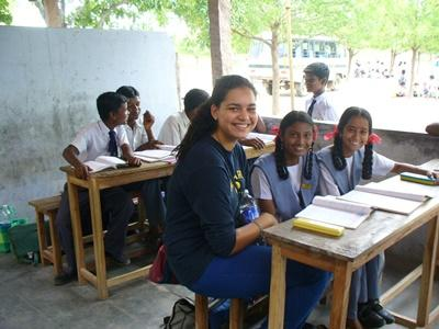 A volunteer sits with her students in a classroom in India, Asia.