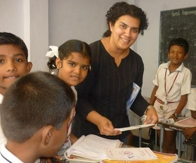 A volunteer smiles with her students in a school in India, Asia.