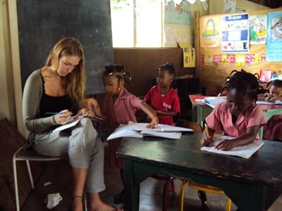 A Teaching volunteer in Jamaica corrects the work of the children in her class