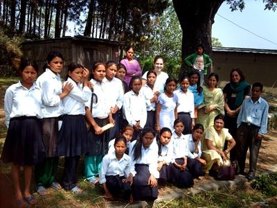 A  volunteer poses with her students and colleagues outside the school in Nepal, Asia.