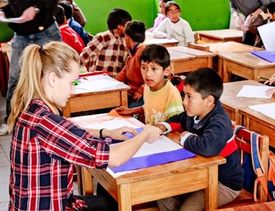 A volunteer helps two of her little students in a classroom in Peru, Latin America.