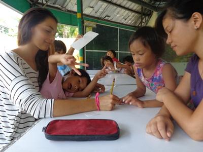 A volunteer smiles with her students in a school in the Philippines,  Asia.