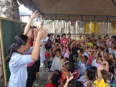 Volunteers and local staff playfully interact with their students in a school in the Philippines, Asia.