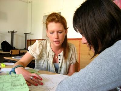 A Projects Abroad volunteer helps her student with her homework at a school in Romania, Eastern Europe