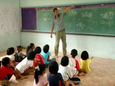 A volunteer teaches his class in Thailand.