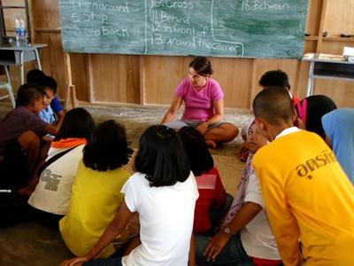 A volunteer sits with her class in Thailand, Asia.