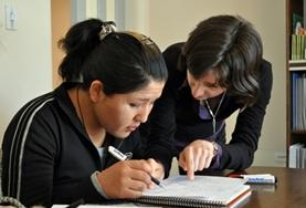 A Teaching volunteer gives a one-on-one English lesson to a local student at a school in Bolivia.