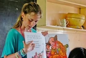 A Teaching volunteer points to the words as she read an English book to school children in Fiji.