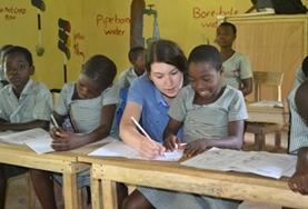 A volunteer assists a child with school work on a Teaching Project placement in Ghana