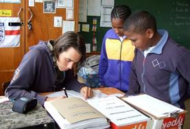 Two school children watch as a Teaching volunteer demonstrates how to complete the English homework assigned to them.