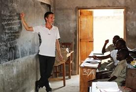 A Teaching volunteer demostrates a lesson on a blackboard to a class of school students in Togo.