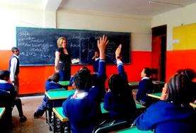 Children raise their hands during a lesson hosted by a French teaching volunteer in Ethiopia