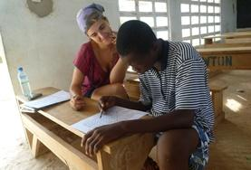 A volunteer French teacher assists a students with his work at a placement in Togo